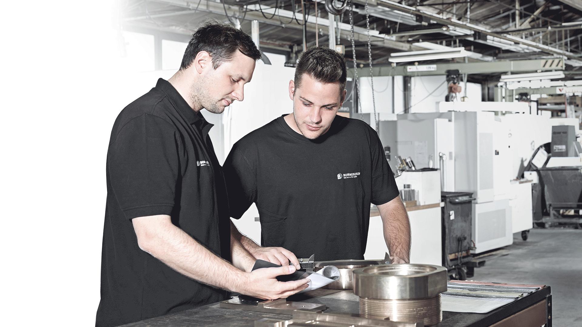 Zwei Männer in einer Produktionshalle die an einem Produkt arbeiten.