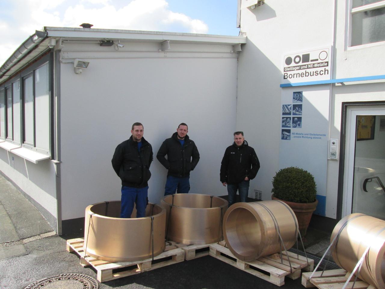 Drei Männer mit Produkten vor dem Gebäude der Christoph Bornebusch GmbH